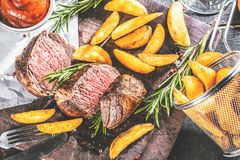 Bistecca di manzo deliziosa con i potatos e semi e rosmarin del pepe fotografia stock libera da diritti
