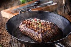 Bistecca di manzo Fette medie succose della bistecca di Rib Eye sul bordo di legno con le spezie ed il sale delle erbe del coltel Fotografia Stock Libera da Diritti