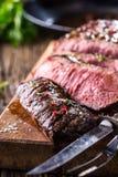 Bistecca di manzo Fette medie succose della bistecca di Rib Eye sul bordo di legno con le spezie ed il sale delle erbe del coltel Immagine Stock