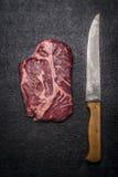 Bistecca di manzo fresca con i trincianti sulla vista superiore del fondo rustico scuro fotografia stock