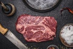 Bistecca di manzo fresca con il mulino di pepe della pentola del trinciante del pepe e del sale sulla fine scura rustica di vista fotografia stock