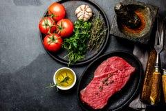 Bistecca di manzo fresca della carne cruda Filetto di manzo, spezie, erbe e coltelleria d'annata Priorità bassa dell'alimento con fotografia stock