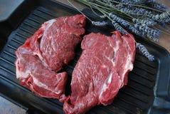 Bistecca di manzo fresca su una griglia con il ramo della lavanda Fotografie Stock Libere da Diritti