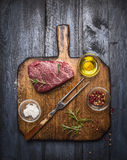 Bistecca di manzo marmorizzata fresca cruda con la forcella della carne e condimenti sul tagliere rustico sopra fondo di legno bl fotografia stock libera da diritti