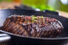 Bistecca di manzo Bistecca succosa di Rib Eye in pentola sul bordo di legno con l'erba ed il pepe Immagine Stock Libera da Diritti