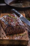 Bistecca di manzo Bistecca succosa di Rib Eye in pentola sul bordo di legno con l'erba ed il pepe Fotografia Stock