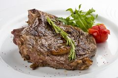 Bistecca di Ribeye con i rosmarini Su un piatto bianco immagini stock