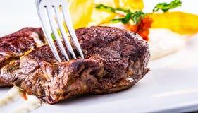Bistecca di scamone Chiuda sulla carne arrostita tenera del manzo sul piatto bianco con la decorazione di verdure immagine stock libera da diritti