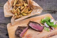 Bistecca di scamone superiore arrostita rara media con le patate arrostite Immagini Stock