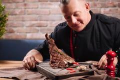 Bistecca di spezzettamento contentissima dell'uomo con le verdure Fotografie Stock