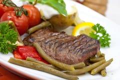 Bistecca di striscia della lombata con i fagioli verdi, pomodoro, pepe Immagini Stock Libere da Diritti