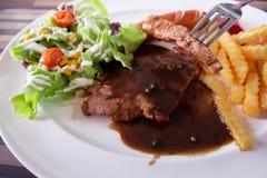 Bistecca e patate fritte della carne di maiale sul piatto Immagine Stock