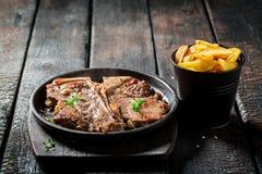 Bistecca e patatine fritte di bistecca con l'osso saporite con sale e pepe fotografia stock