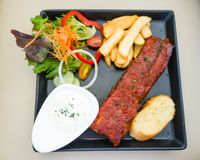 Bistecca ed insalata di manzo sul piatto nero Fotografia Stock