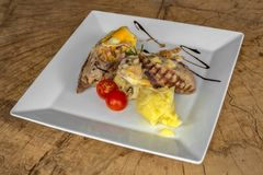 Bistecca farcita del pollo in un piatto bianco su un fondo di legno fotografie stock