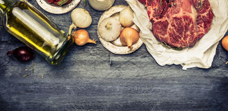 Bistecca marmorizzata cruda della carne con petrolio e le spezie su fondo di legno rustico Insegna per il sito Web con la cottura Fotografia Stock