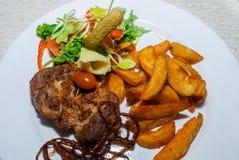 Bistecca nella lombata arrostita esperta con le spezie e le erbe fresche pomodoro fresco, patate al forno e peperoncini roventi Fotografia Stock Libera da Diritti