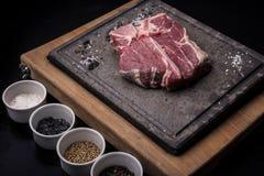 Bistecca nella lombata cruda con le spezie ed il sale su fondo di pietra scuro, vista superiore fotografia stock