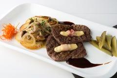 Bistecche arrostite della carne con le verdure, i sottaceti, la salsa e la decorazione immagini stock libere da diritti