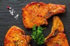 Bistecche arrostite della carne di maiale, cotolette con le ossa e prezzemolo fresco su fondo di pietra nero, vista superiore Fotografia Stock