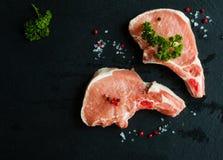 Bistecche crude della carne di maiale, cotolette grezze con le ossa e prezzemolo fresco su fondo di pietra nero, vista superiore Fotografia Stock