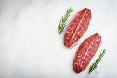 Bistecche crude della lama della cima della carne fresca su fondo leggero Vista superiore con lo spazio della copia fotografie stock