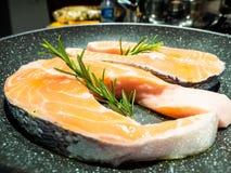Bistecche del salmone, in una pentola, con i rosmarini, fotografie stock
