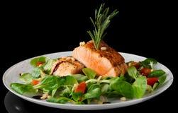 Bistecche di color salmone fritte rare sul nero Immagine Stock