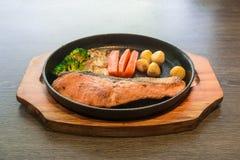 Bistecche di color salmone fritte sulla pentola calda fotografie stock