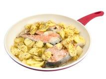 Bistecche di color salmone in una padella con le patate fritte Fotografia Stock