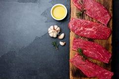 Bistecche di manzo fresche della carne cruda Filetto di manzo sul bordo di legno, spezie, erbe, olio sul fondo di gray di ardesia immagine stock