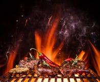 Bistecche di manzo sulla griglia con le fiamme Fotografie Stock Libere da Diritti
