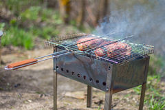 Bistecche e griglia della carne di maiale sul fuoco bruciante Fotografia Stock