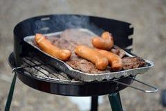 Bistecche e salsiccie sulla griglia, primo piano fotografia stock libera da diritti