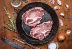 2 bistecche fresche crude della carne di maiale in vecchia padella della ghisa con l'aglio e le erbe della cipolla sulla fine di  Fotografie Stock Libere da Diritti