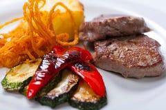 Bistecche fritte della carne di maiale con le patate, i peperoni e lo zucchini fotografia stock