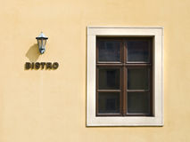Bistro Facade. Minimalist composition of the facade of a Bistro, with a lamp and a window on the orange wall Stock Images