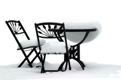 Bistro Set on White. Garden furniture after a snowstorm royalty free stock photos