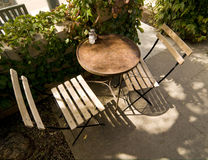 Bistro Table. Charming and Rustic Bistro Table and Two Chairs in Romantic Garden Setting Royalty Free Stock Photography