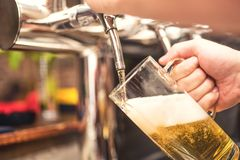 Bistro waiter serving a cold beer. Hand of barman pouring a lager beer from tap Royalty Free Stock Photography