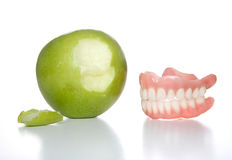 Bit the apple. False teeth just took a bit out of an apple stock photos