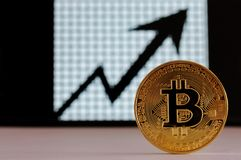 Bit coin gold, physical coin and unfocused chart background, virtual finance, internet money royalty free stock photo