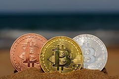 Bit coin gold, silver and bronze coin and printed encrypted money, crypt currency concept in a beach sand royalty free stock photography