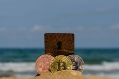 Bit coin gold, silver and bronze coin and printed encrypted money, crypt currency concept in a beach sand stock image