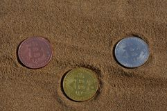 Bit coin gold, silver and bronze coin and printed encrypted money, crypt currency concept in a beach sand stock photo