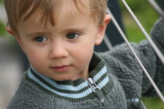 Bit shy. Small kid with a serious face watching parents Royalty Free Stock Image