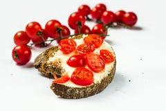 Bita taget bröd med många den lilla körsbärsröda tomaten Arkivfoton