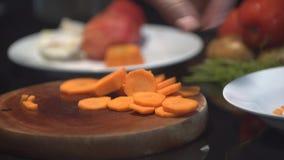 Bitande övre för kock en morot med en kniv arkivfilmer