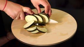 Bitande aubergine för kvinna på ett träbräde Närbild stock video