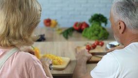 Bitande grönsaker för äldre gift par i kök, matlagningmatställe tillsammans lager videofilmer